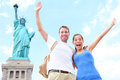 Travel tourists couple at statue of liberty usa new york city multiracial tourist on summer vacation holidays cheering Royalty Free Stock Photos