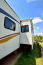Travel trailer in camp in sunshine day under blue sky with tree and flower shown as enjoy wonderful trip and holiday or featured Stock Photography
