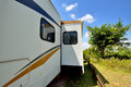 Travel trailer in sunshine day under blue sky camp with tree and flower shown as enjoy wonderful trip and holiday or featured Stock Photos