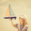 Travel and vacations concept happy kid playing with toy sailing boat against summer sky background Royalty Free Stock Photography