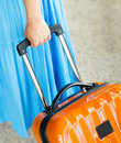 Travel woman in blue dress holds orange suitcase in hand Stock Photography