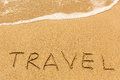 Travel - written manually on the texture of sea sand Royalty Free Stock Photo