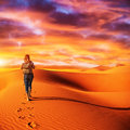 Traveler in the desert traveller active young woman trekking hot sandy wilderness dramatic sunset summertime adventure extreme Royalty Free Stock Images