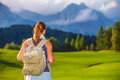 Traveler girl in the mountains rear view of woman with backpack looking on beautiful landscape travel to alps summer adventure Royalty Free Stock Photos