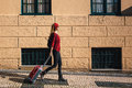 Traveler girl walking in city with red suitcase. Europe.