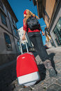 Traveler girl walking in city with red suitcase. Summer.