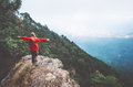 Traveler hands raised standing on mountains cliff Royalty Free Stock Photo