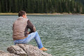 Traveler Man enjoying mountain lake view. Man looking at  horizon, loneliness concept. Royalty Free Stock Photo