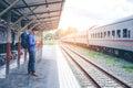 Traveler man waits train on railway platform Royalty Free Stock Photo