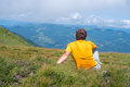 Traveler sitting on an alpine meadow, among lush grass Royalty Free Stock Photo