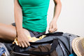 Traveler struggling with suitcase woman trying to close sitting on it Stock Photo