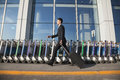 Traveler walking fast next to row of luggage carts at airport Royalty Free Stock Photo