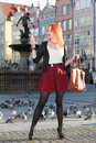 Traveler woman red hair girl with smart phone old town gdansk haired fashion outdoors in european city neptune fountain in the Stock Photography