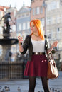 Traveler woman red hair girl with smart phone old town gdansk haired fashion outdoors in european city neptune fountain in the Royalty Free Stock Images