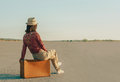 Traveler woman sitting on suitcase on road, copy-space Royalty Free Stock Photo