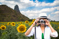 Traveler women covering her face with the camera in the sunflower field Royalty Free Stock Photo