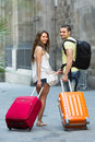 Travelers with baggage in the street positive smiling tourist couple heading to hotel on foot Stock Images