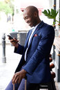 Traveling businessman reading text message smiling young african with travel bag on mobile phone Stock Photos