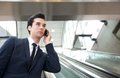 Traveling businessman talking on the phone on escalator portrait of a Royalty Free Stock Photo