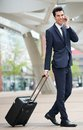 Traveling businessman talking on phone outdoors portrait of a Royalty Free Stock Photography