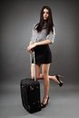 Traveling businesswoman beautiful young with luggage over gray background concept Royalty Free Stock Photography