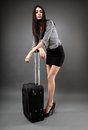 Traveling businesswoman beautiful young with luggage over gray background concept Stock Images
