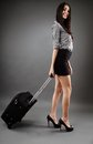 Traveling businesswoman beautiful young with luggage over gray background concept Royalty Free Stock Images