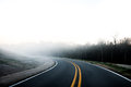 Traveling on a curved highway approaching fog asphalt vehicle skid marks that run off of the Royalty Free Stock Photo