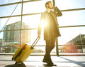 Traveling man walking and talking on mobile phone at airport Royalty Free Stock Photo