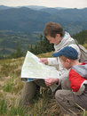 Traveling people reading map on mountains Stock Images