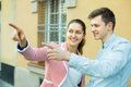 Traveller asking woman direction friendly young women to show him focus on man Stock Photo