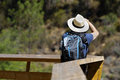 Traveller back view from a with a backpack and hat taking photos Royalty Free Stock Photography
