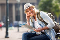 Traveller holding map pretty female a and sitting on bench in the city Stock Photography