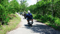 Traveller make a tour by motobike ca mau viet nam june mororbike taxi driver take on the way to u minh jungle they ride in curve Stock Photo