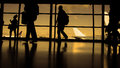 Travellers with suitcases and baggage in airport walking to departures in front of window, silhouette, warm Royalty Free Stock Photo