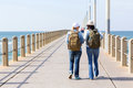 Travellers walking pier on a beach during thier holiday vacation Stock Image