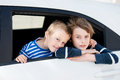 Travelling children two in the car and peeking in the window Royalty Free Stock Photo