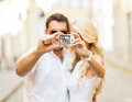 Travelling couple taking photo picture with camera summer holidays travel vacation tourism and dating concept Royalty Free Stock Images