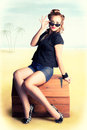 Travelling Pin-Up Girl Sitting On Vintage Luggage Royalty Free Stock Photography