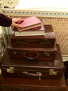 Travelling a stack of olden styled luggage with a hand reaching for some books Royalty Free Stock Photography