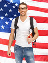 Travelling student bright picture of with backpack and book over american flag Royalty Free Stock Photography