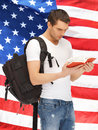 Travelling student bright picture of with backpack and book over american flag Royalty Free Stock Photos