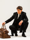 Travelling young man in a suit with a brown vintage style suitcase Royalty Free Stock Photo