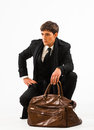 Travelling young man in a suit with a brown vintage style suitcase Royalty Free Stock Photography