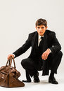 Travelling young man in a suit with a brown vintage style suitcase Royalty Free Stock Images