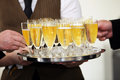 Tray of chilled champagne in elegant flutes being carried by a waiter at a catered event with male hands helping themselves to a Stock Photo