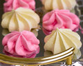 Tray of meringues yellow and pink on a Stock Photo
