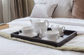 Tray of white tea set on bed in bedroom Stock Photos