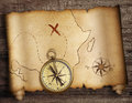 Treasure map roll with old compass on table top Royalty Free Stock Photo