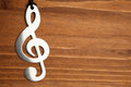 Treble clef on brown wooden background Stock Photos